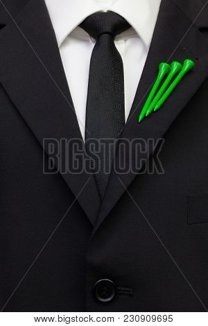The Detail Of Wedding Suit With Golf Design. Green Golf Tees On The Flap Of Black Jacket.