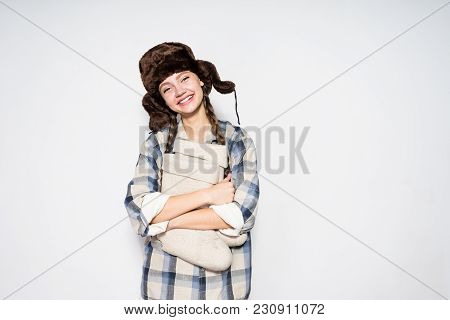 Happy Young Russian Girl Smiling, Wearing A Warm Fur Hat, Holding Gray Felt Boots