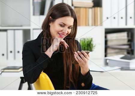 Beautiful Brunette Woman In Office Hold Phone At Workplace Portrait. Read News Mania Send Sms Chat A