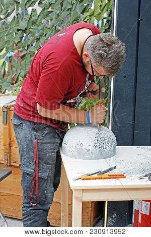 Moscow, Russia - June 09, 2017: Stonemason Processes A Spherical Stone With A Chisel And A Hammer At