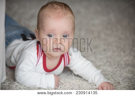 Innocence, beauty, purity. Child development concept. Baby with blue eyes on adorable face. Childhood, infancy, newborn. Infant crawl on floor carpet. poster