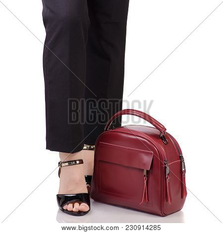 Female Legs In Classic Black Pants Black Lacquer Shoes With Red Leather Handbag In Hand Fashion Beau