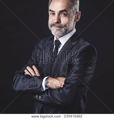 Successful Businessman With Arms Crossed On Black Background.the Photo Has A Empty Space For Your Te