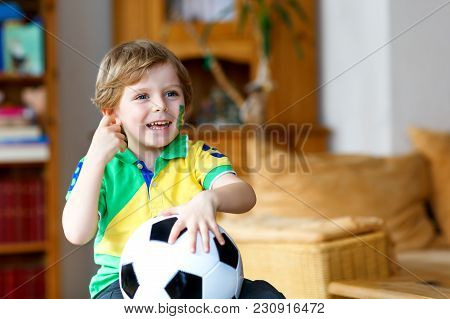 Little Blond Adorable Kid Boy With Ball Watching Soccer Football Cup Game On Tv. Funny Happy Crying