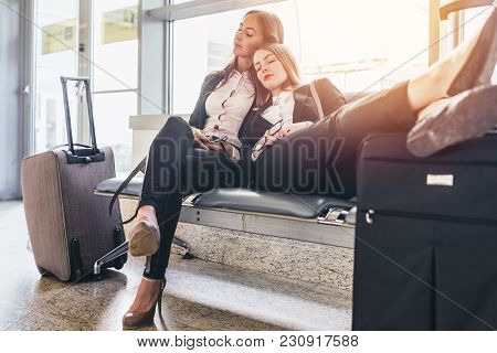 Two Tired Female Tourists Sleeping Sitting On Bench With Baggage Near Them In Waiting Room In Airpor