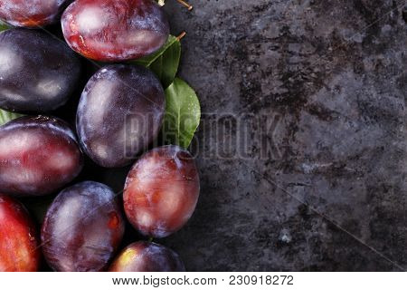 Ripe Plums Scattered On A Black Background, Space For Text