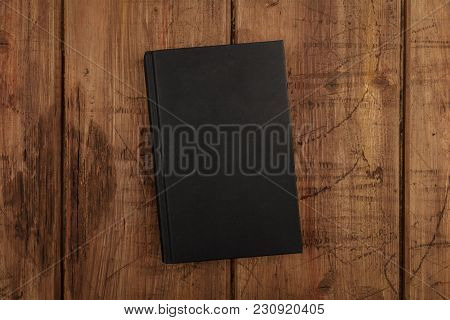 An Overhead Photo Mockup Of A Black Book On A Dark Rustic Background, With A Place For Text