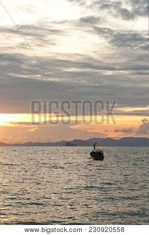 Beautiful Tropical Sunset With Longtail Boat Silhouette On Background