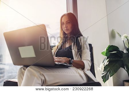 Elegant Businesswoman Writing Texts Using Laptop Sitting On Armchair In Loft Apartment.
