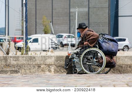 La Rochelle, France - July 23, 2015 : Homeless, Disabled Poor Man Sitting On Wheelchair At The Stree