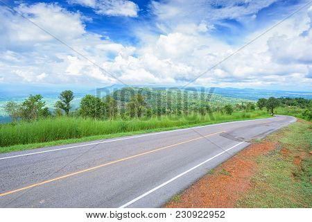Asphalt Road In Mountain Forest With Blue Sky