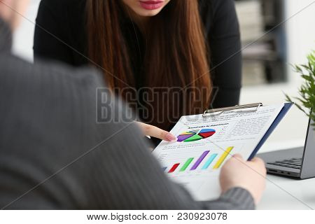 Female Arm Holding Silver Pen Point In Financial Graph Solving And Discussing Problem With Colleague