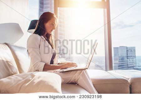 Side View Of Successful Young Female Working On Laptop.