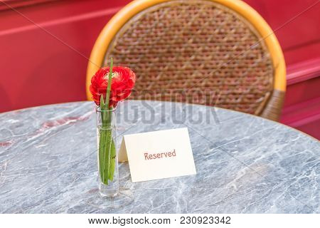 Red Ranunculus Single Flower  On Table With Resrved Plate