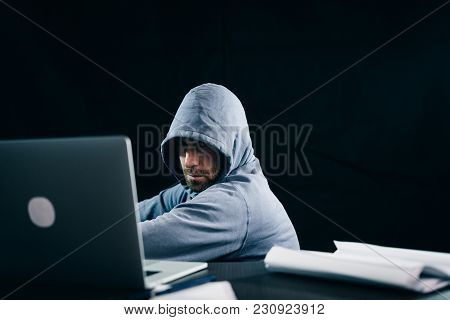 Mysterious Bearded Man Hacker Hides His Face Under The Hood, Doing Something Illegal On The Laptop