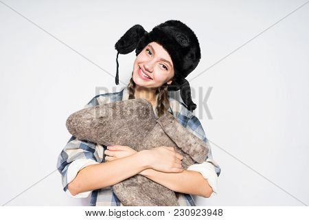 Happy Young Russian Girl Smiling, Wearing A Warm Fur Hat, Holding Gray Winter Boots