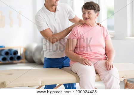 Physiotherapist Massaging Smiling Senior Woman