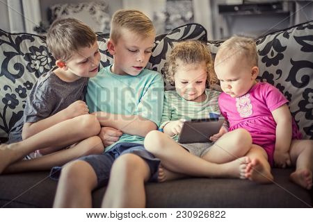 Group of kids playing with an electronic tablet devices