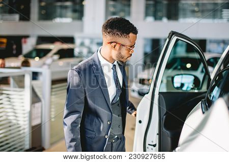 Young African American Driver Opening His New Car Door