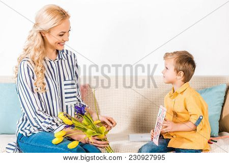 Son Gifting Smiling Mother Bouquet And Postcard On Mothers Day