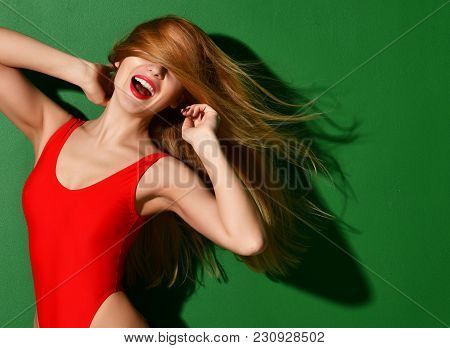 Young Happy Beautiful Sexy Woman Posing In Red Summer Fashion Body Swimsuit With Windy Hair On Green