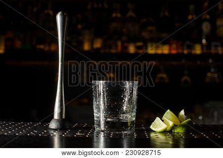 Itrus Press, Cocktail Glass And Slices Of Lime Arranged On The Bar Counter Against The Backgound Of