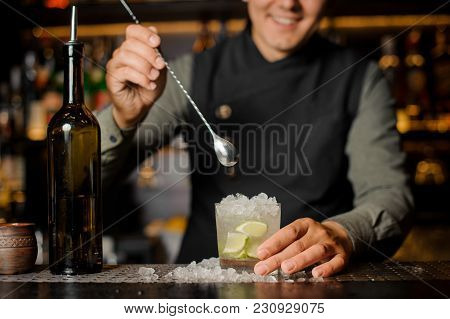 Smiling Barman Stirring Fresh Mojito In A Cocktail Glass Using A Spoon On The Bar Counter