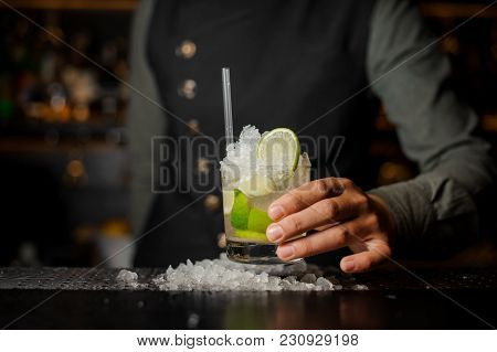 Barman Hand Holding A Glass With A Fresh Mojito Cocktail With Sour And Sweet Taste On The Bar Counte