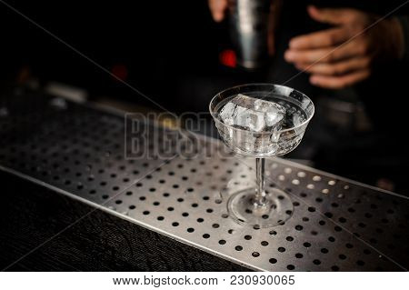 Elegant Cocktail Glass Filled With Fresh Alcoholic Drink With A Big And Faceted Piece Of Ice On The