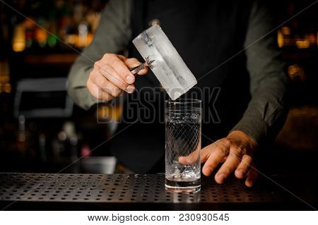 Barman Putting A Big Rectangular Piece Of Ice Into A Cocktail Glass For Making A Tasty Alcoholic Dri