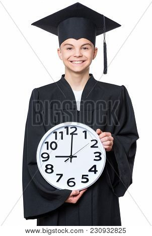 Portrait Of Graduate Teen Boy Student In Black Graduation Gown With Hat, Holding Big Clock - Isolate