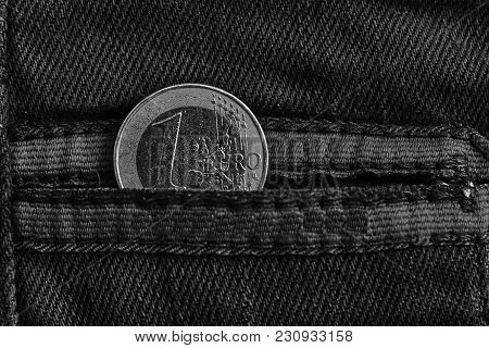 Monochrome Euro Coin With A Denomination Of 1 Euro In The Pocket Of Worn Blue Denim Jeans With Red L