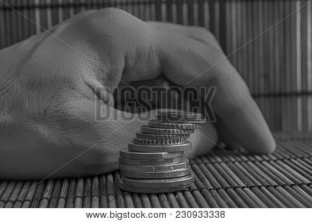 Monochrome Pile Of Euro Coins, Like A Tower Lies On Wooden Bamboo Table Background.