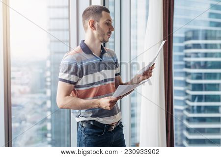 Businessman Holding Reading Documents Standing By The Window In Office.