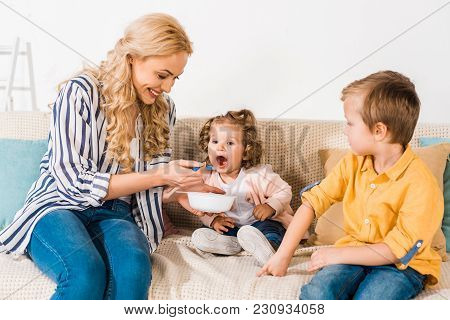 Smiling Mother Feeding Cute Little Daughter At Home