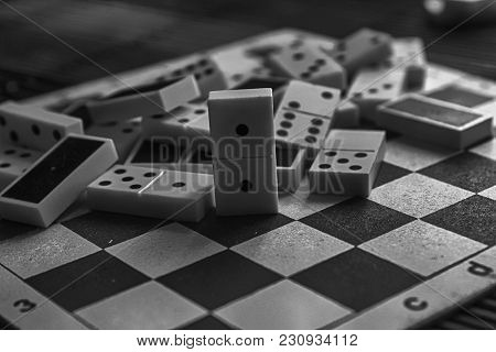 Monochrome Chaotic Pile Of Domino Pieces On The Bamboo Brown Wooden Table Background