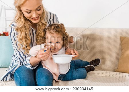 Happy Mother Feeding Adorable Little Daughter And Holding Plate With Spoon At Home