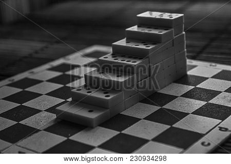 Monochrome Pyramid Of Domino Pieces On The Bamboo Brown Wooden Table Background