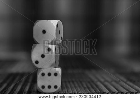 Monochrome Stack Of Three White Plastic Dices On Brown Wooden Board Background. Six Sides Cube With