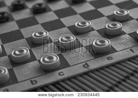 Monochrome Checkers In Checkerboard Ready For Playing. Game Concept. Board Game. Hobby. Checkers On