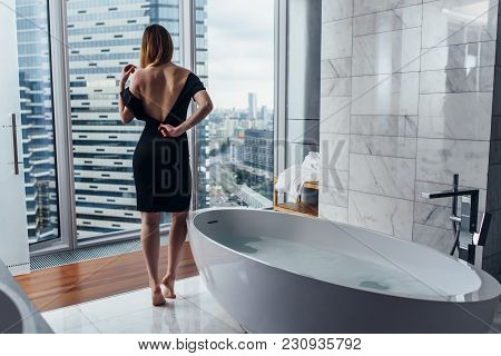 Back View Of Young Woman Wearing White Bathrobe Standing In Bathroom Looking Out The Window With Bat