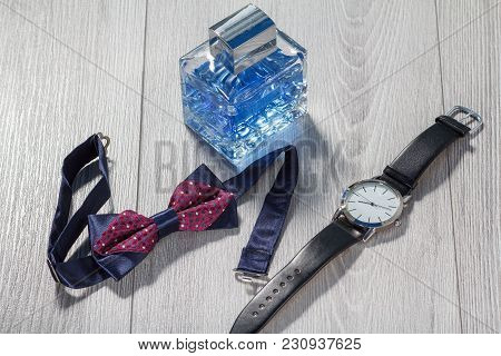 Man Perfume, Watch With A Black Leather Strap And Bow Tie On Grey Wooden Background. Men Accessories