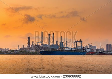 Oil And Gas Refinery Plant With Shipping Loading Dock At Sunrise.