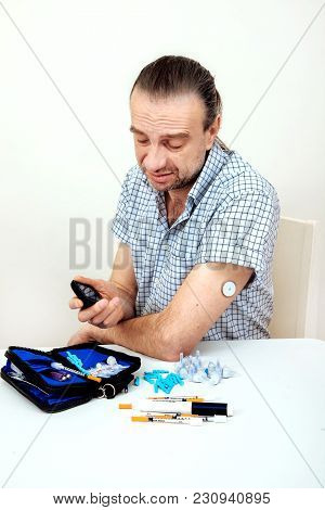 Man Testing Glucose Level With A Digital Glucometer, Sensor Checkup Glucose Levels Without Blood. Di