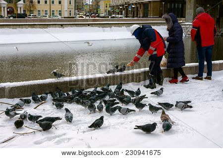 Group Of People Feed With Bread Crumbs Ducks And Pigeons On The River In Winter.