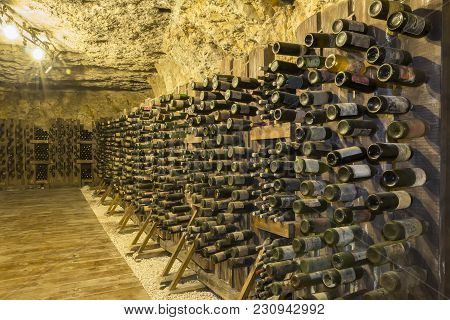 Many Old Wine Bottles Stacked On Wooden Racks In A Cellar