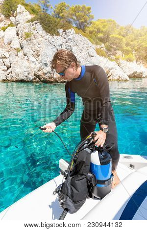 Male Scuba Instructor Is Checking His Equipment