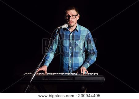Musician Playing On Keyboard Electric Piano And Singing On Dark. Musician Concept.