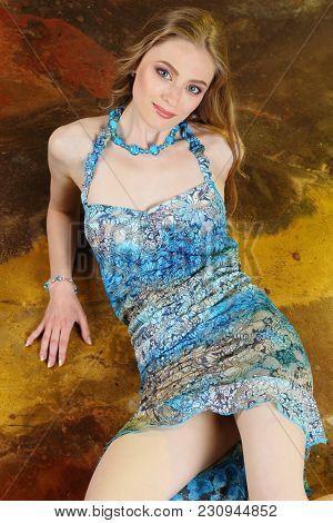 Portrait Of Attractive Young Adult Slender Girl Sitting In Summer Short Blue Dress. The Beautiful Wo