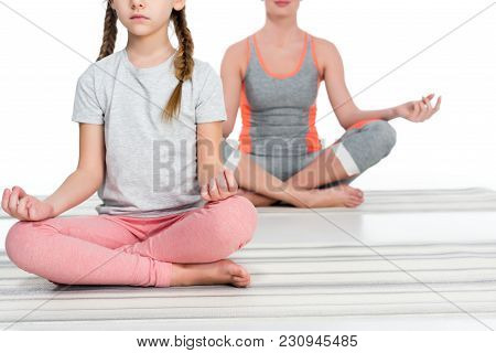 Partial View Of Athletic Mother And Daughter Practicing Yoga On Mats Together Isolated On White